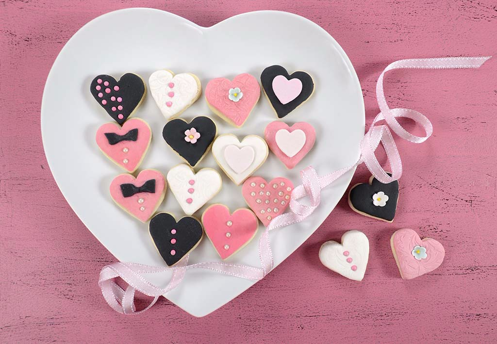 Pink, black and white homemade heart shape cookies on white hear
