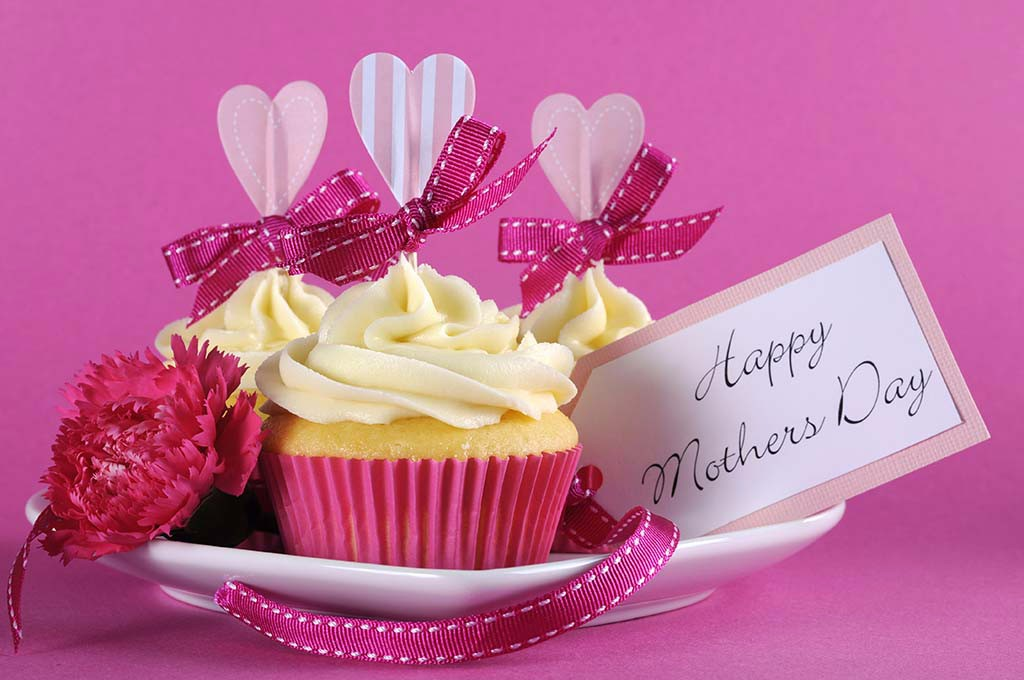 Happy Mothers Day cupcakes on pink background